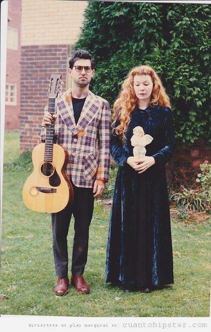Padre y madre hipster con guitarra y escultura de ángel en el jardín