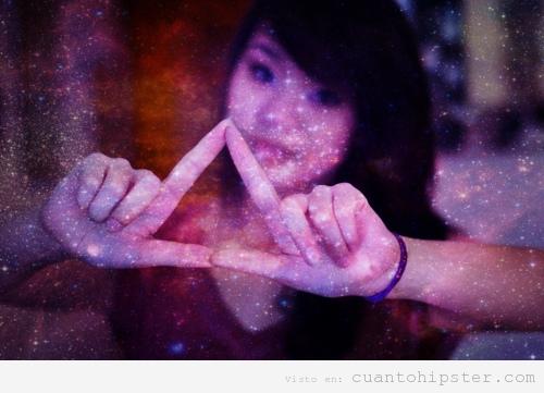 Chica asiática hace el triángulo hipster con la mano y fondo imagen cósmico