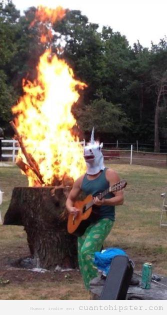 Hipster con cabeza de unicornio tocando la guitarra al lado de una hoguera