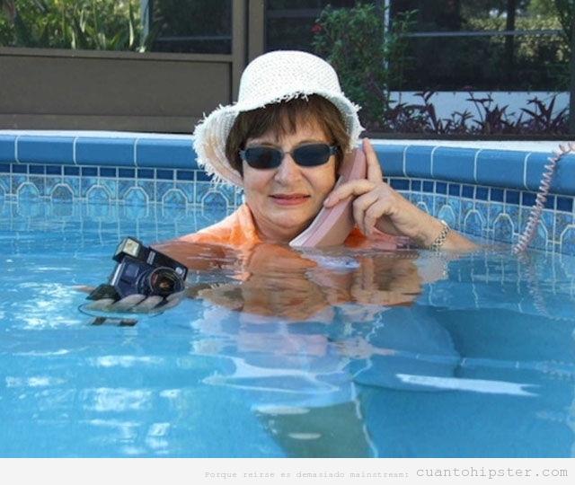 Abuela hipster en la piscina con ropa, teléfono  cámara antigua