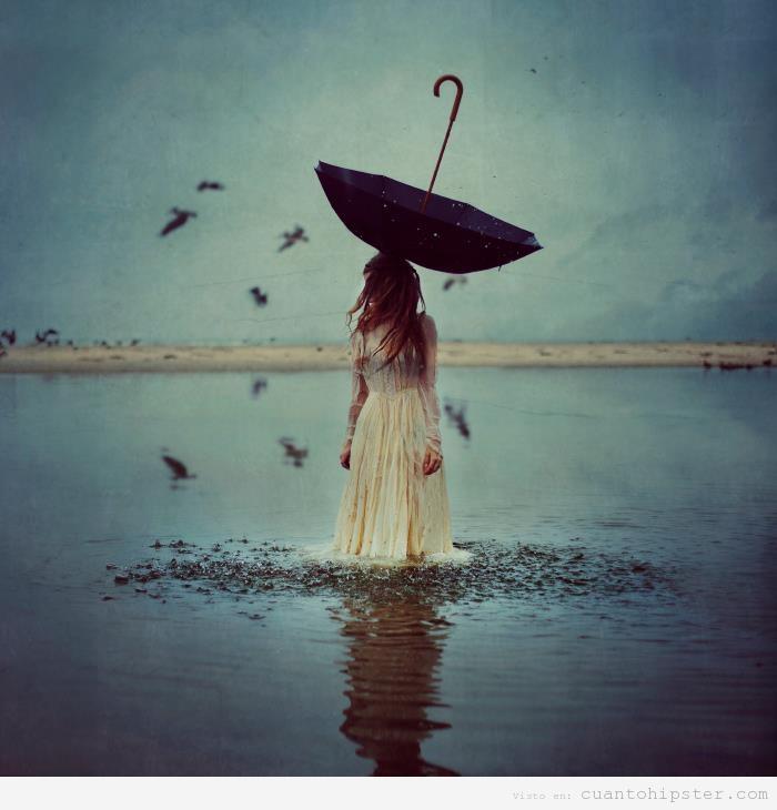 Foto hipster bonita de una mujer en el agua con un paraguas del revés en la cabeza