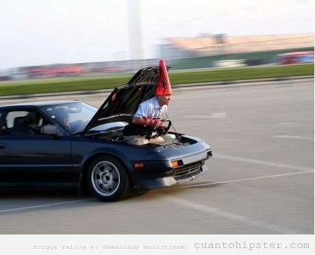 Hombre hipster conduciendo un coche metido en el capó