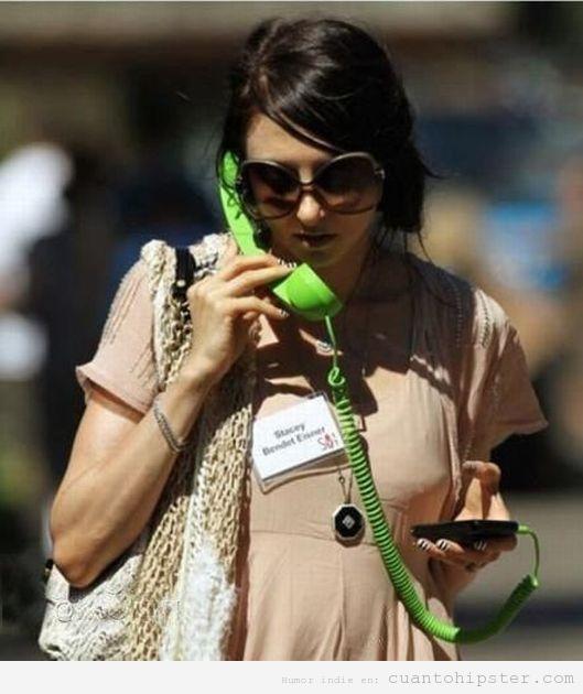Chica hipster con el gadget de teléfono retro como auricular para su iphone