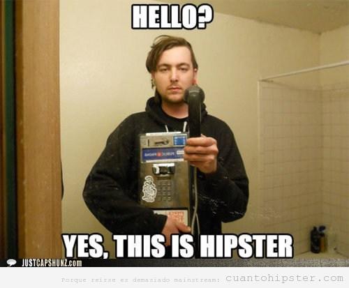 Chico hipster haciéndose una autofoto en el baño con una cabina de teléfonos antigua
