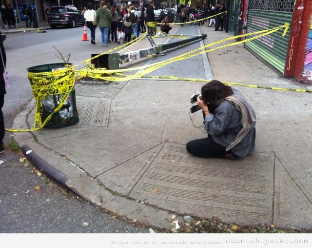 Hipster hace una foto con una cámara antigua a una papelera