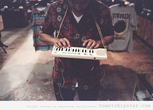 Foto hipster de un chico con un teclado casio colgado del cuello