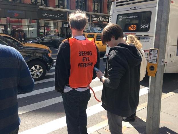 Hombre guía para personas que andan por la calle mirando el móvil