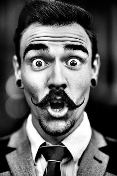 Foto de un chico con bigote y look hipster y con cara de sorpresa
