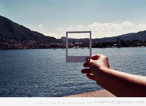 Hipster con un marco de Polaroid por el mundo