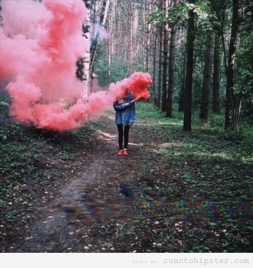 Foto de una chica con una bengala de humo en el bosque
