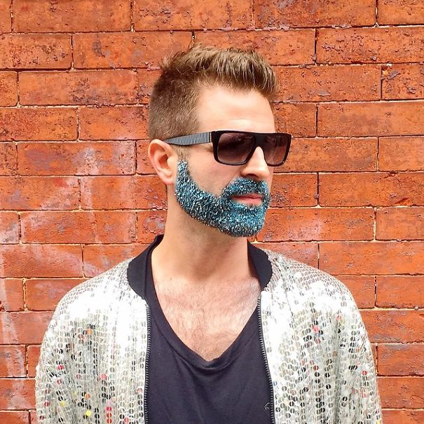 Foto de un chico hipster con la barba llena de purpurina