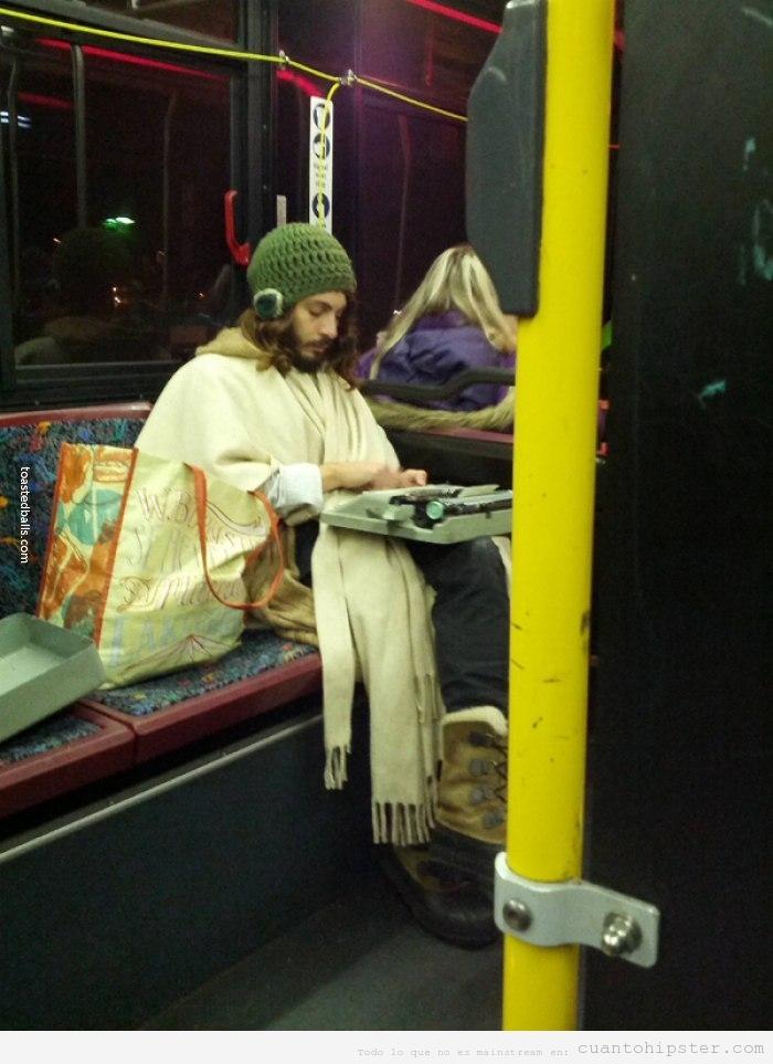 Foto de un chico hipster en el tranvía escribiendo a máquina