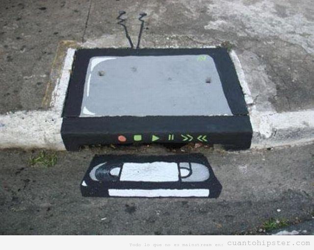 Pintura callejera hipster con una television y un vhs metido en una alcantarilla