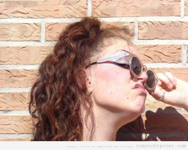 Chica hipster con gafas de sol hipsters y cara de asco