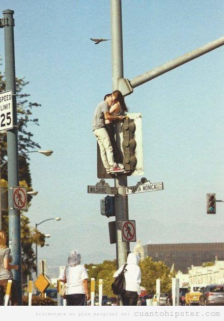 Pareja de hipsters se dan un beso subidos a un semáforo