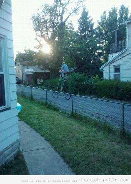 Bicicleta hipster muy alta dando paseo por el vecindario