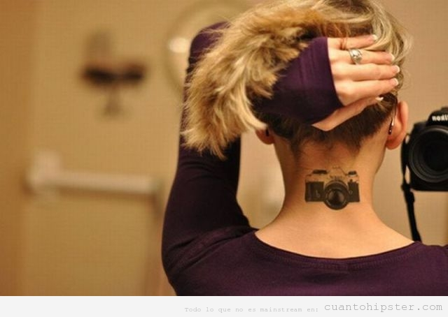 Chica hipster con un tatuaje de una cámara de fotos reflex en la nuca