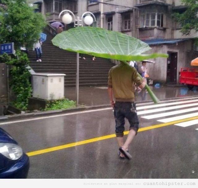 Chico hipster por la calle con un paraguas de una hoja de vegetal gigante