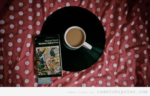 Imagen bonita indie y hipster de una taza de café posada sobre un vinilo y la novela 1984 de Orwell