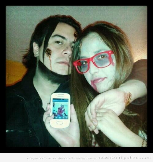 Chico y chica disfrazados de hipsters zombies en Halloween