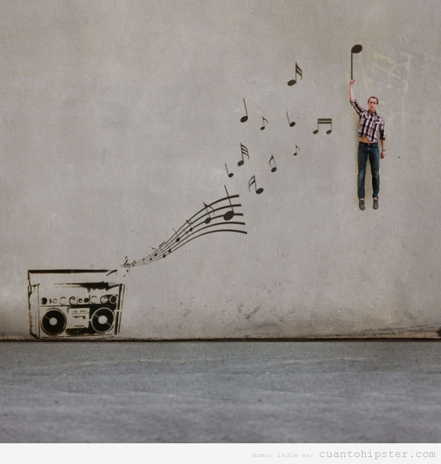 Foto bonita de un chico que vuela gracias a una nota musical de un graffiti