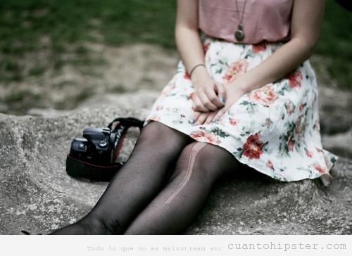 Imagen de una chica con ropa vintage, las medias rotas y cámara reflex
