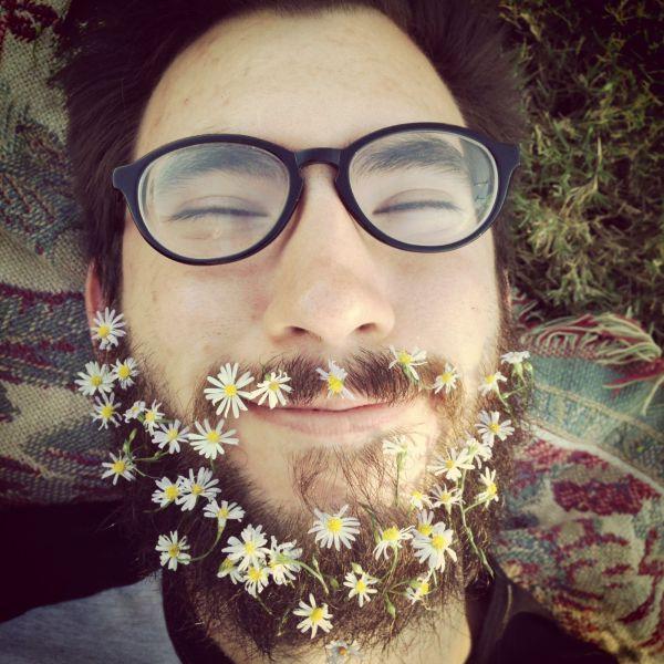 Foto graciosa de un hipster feliz con margaritas en la barba larga
