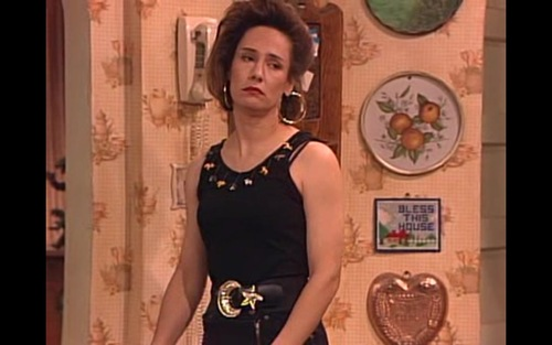 Hipster vestida como Jackie de Roseanne con cinturón dorado
