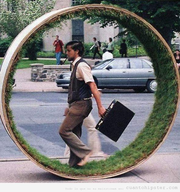 Hipster descalzo andando por una rueda de hierba