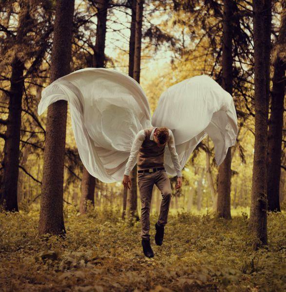 Foto bonita de un chico volando con unas alas de sábanas