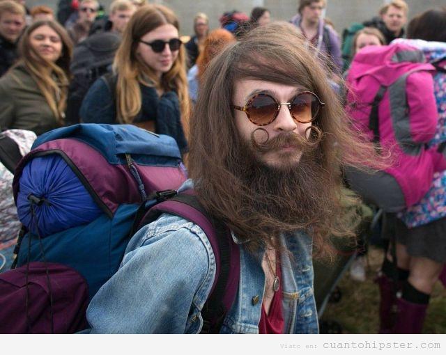Chico look hippie hipster con una mochila en un festival indie