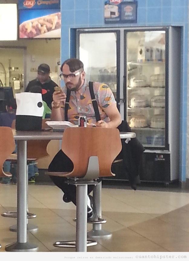 Chico con peinado y look hipster en una pastelería