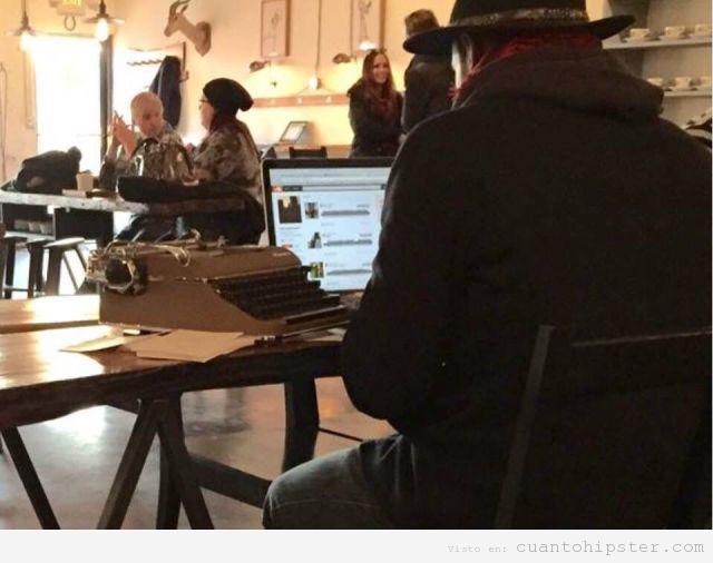 Hipster en una cafetería con la máquina de escribir