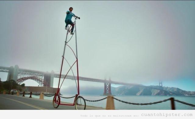 Foto de un hipster en bicicleta muy alta