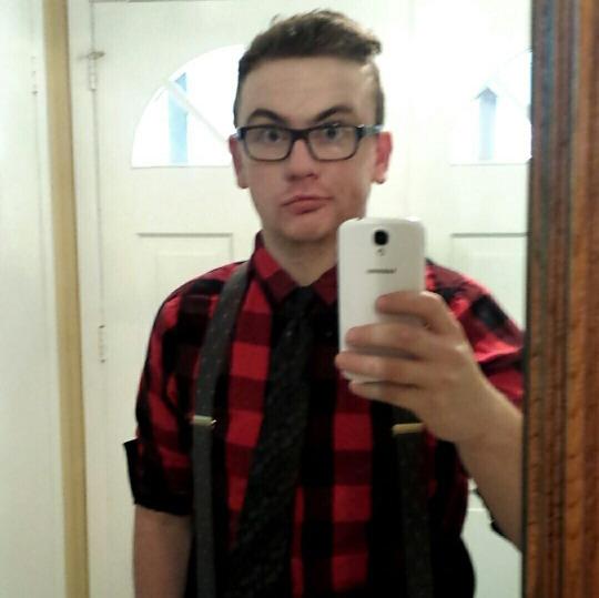 Selfie de un chico con look hipster con camisa cuadros y tirantes
