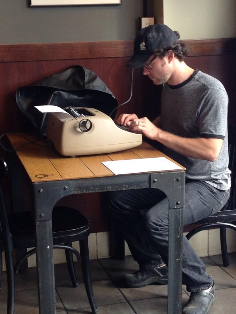 Foto de un hipster que escribe a máquina en una cafetería