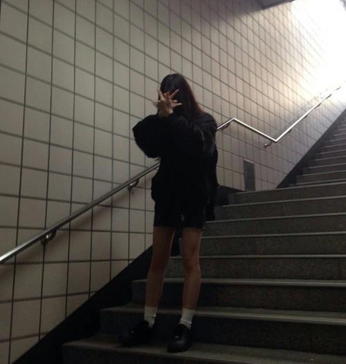 Foto de una chica con look grunge bajando las escaleras del metro