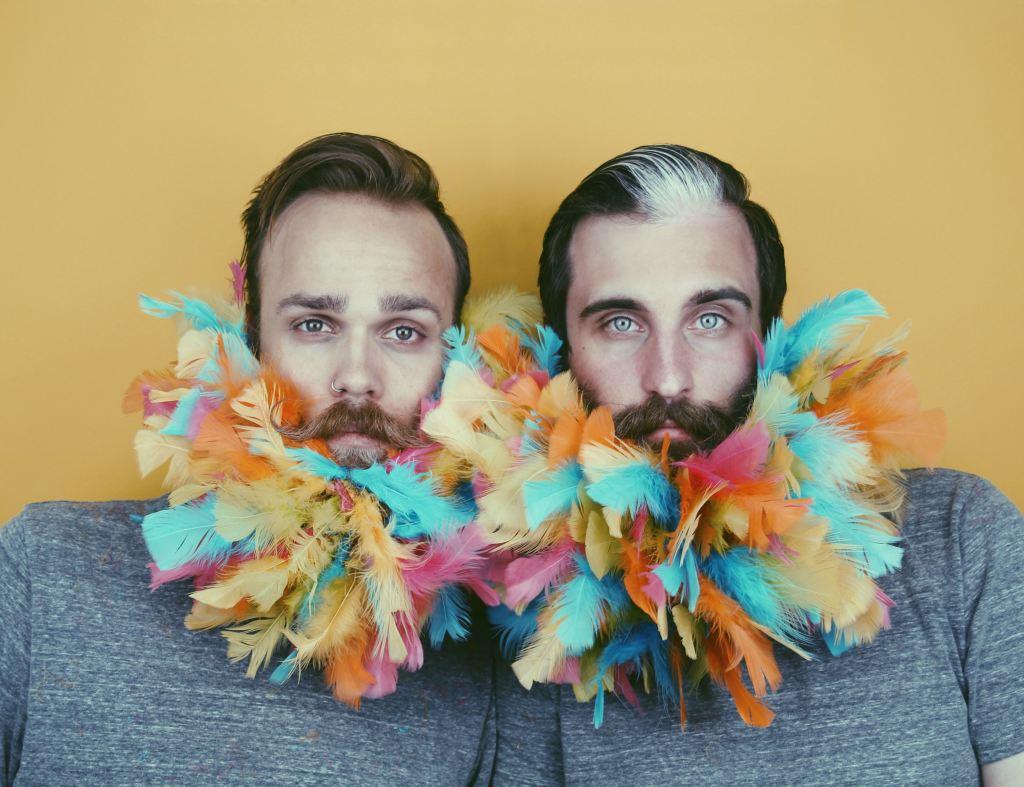 Foto de dos hipsters con plumas en la barba