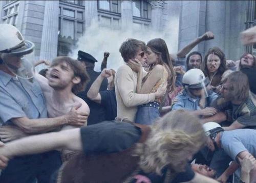 Foto antigua hippies besandose en una manifestación