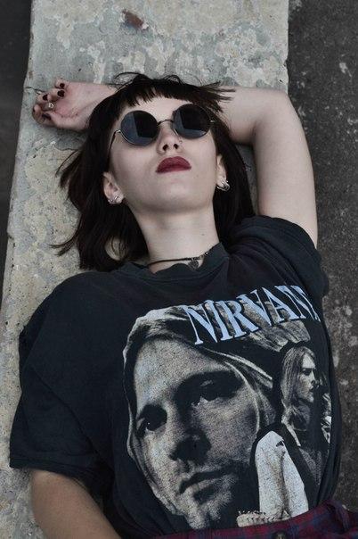 Moda new grunge. gafas de sol redondas y camiseta de Nirvana